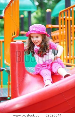 Happy little girl rolling down the hill on the playground