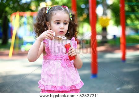 Little girl with tails stands with a jar of soap bubbles on the playground