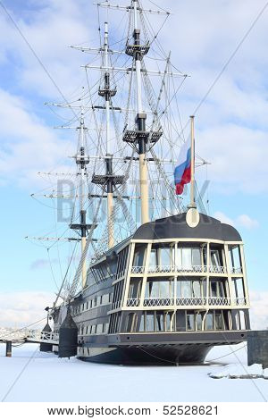 Historical reconstruction of the battleship of the XVIII century with the Russian flag at the pier