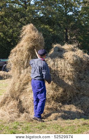 armer is handicraft collecting hay to a haystack during a Dutch agricultural festiva