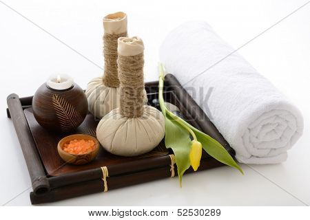 spa still life with spa herbal balls, candlestick, tulip, stones and salt in wooden bowl and white towel over white