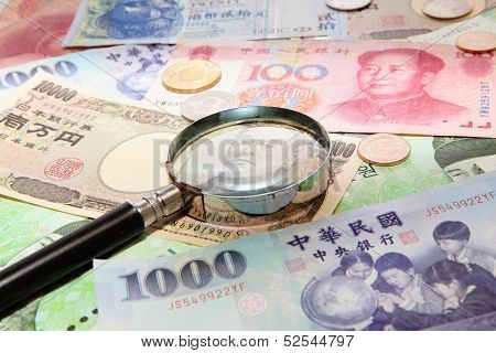 Asian Currency And Magnifying Glass