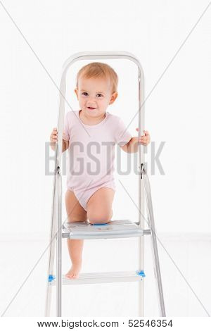 Cute baby girl climbing on ladder wearing bodysuit.