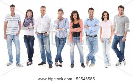 Full-length group portrait of happy young casual people standing side by side, looking at camera, smiling.