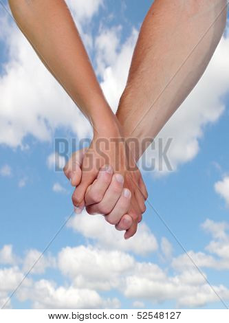 Two hands clasped in love with a blue sky background