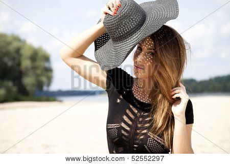 Young adult beautiful brunette woman in black dress and black hat on the beach