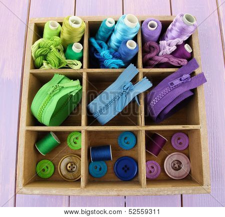 Multicolored skeins of thread with fasteners and buttons in box closeup