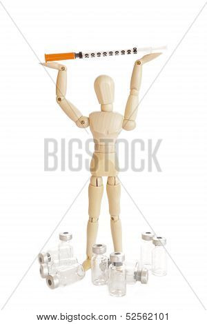 A Wooden figure holding a medicine injector