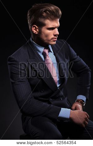 side view of a young fashion model in a classic suit and tie on dark background