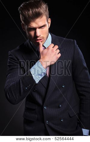 young fashion business man in a provocative pose on dark background