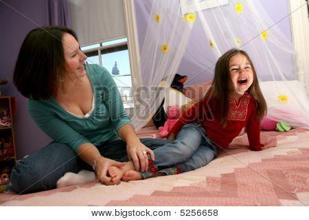 Mother Tickling Her Little Girl's Bare Feet On The Bed