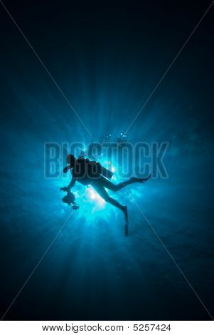The Silhouette Of A Diver With Sunrays