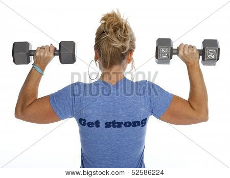 Rear view of woman lifting dumbbells against white background.