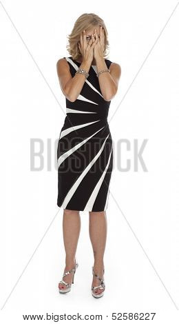 Full length photo on white background of mid-forties woman standing with hands partially covering eyes, wearing a black dress.