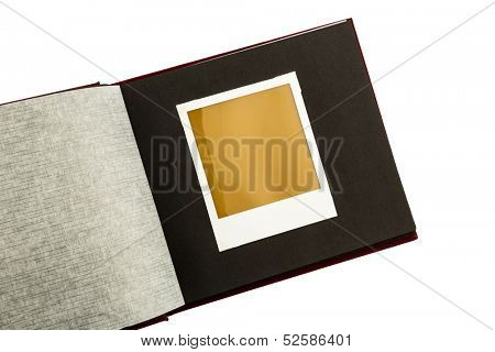 an old photo album with one old empty photo