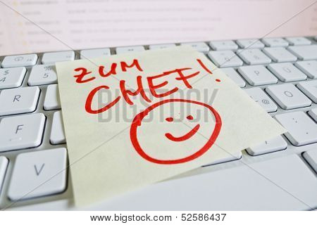 a sticky note is on the keyboard of a computer as a reminder: for chief