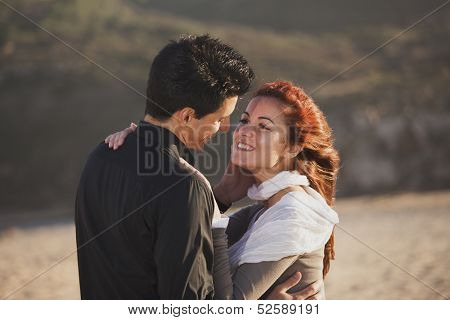 Love and affection between a young couple at the beach in sunny day