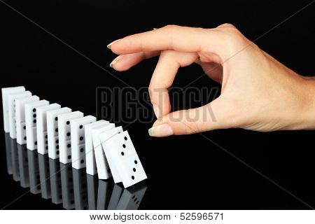 Hand pushing dominoes isolated on black