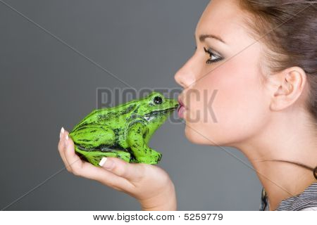 Shot Of A Pretty Teen Kissing A Frog