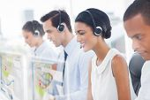 stock photo of hologram  - Call center employees at work on futuristic hologram interfaces in bright modern office - JPG