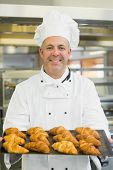 picture of croissant  - Mature baker presenting some croissants on a baking tray - JPG