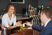 stock photo of tumbler  - Beautiful waitress serving handsome businessman in a classy bar - JPG