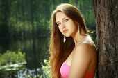 picture of 16 year old  - Beautiful Girl 16 years old with long brown hair and a pink dress stands alone on a green background of the forest and water on a summer day in the sun.