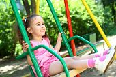stock photo of stroll  - Laughing little girl in a pink dress swinging on a swing at the playground - JPG