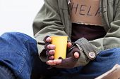 stock photo of beggar  - Hands of homeless person holding a yellow paper cup - JPG