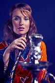 picture of hookah  - Young woman in style of hippie smoking hookah in interior location like room or house - JPG