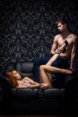 foto of explicit  - Young and beautiful couple on the leather sofa - JPG