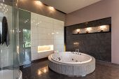 image of tapping  - Round bath in a luxury tiled bathroom interior - JPG