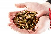 image of 9mm  - a heap of 9mm pistol bullets holded by human hands isolated over a white backgrounds - JPG