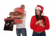 Young couple laden with Christmas presents with the woman standing smiling in the foreground in a fe