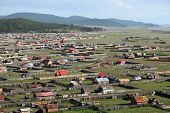 stock photo of ulaanbaatar  - The sweeping remote hills of Mongolia are marked only by primitive roads and clusters of simple cabins - JPG