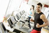 stock photo of cardio exercise  - Young man running on a treadmill at the gym - JPG