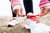 stock photo of dirt road  - Woman runner tying sport shoes - JPG