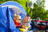 stock photo of tent  - Man and woman hikers camping in summer nature - JPG