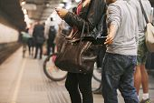 stock photo of stealing  - Thief stealing wallet from purse of a woman using mobile phone at the subway station - JPG