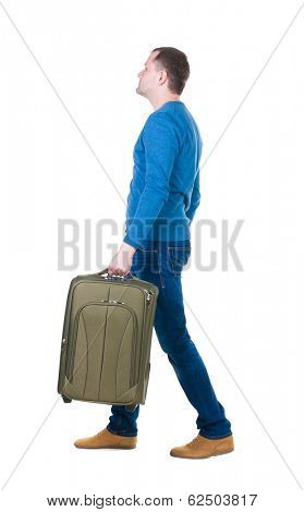 back view walking man with suitcase.  brunette guy in motion. backside view of person.  Rear view people collection. Isolated over white background. young man goes to side rolling travel bag on wheels