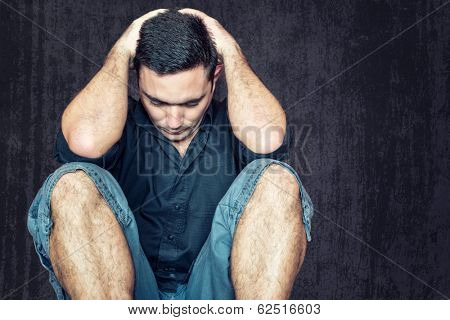 Lonely and sad young man sitting on the floor with his head between his hands