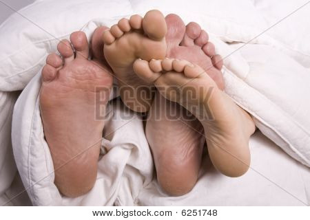 Man And Woman's Feet Together Under Covers