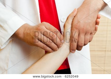 Chinese doctor checking a patients pulse