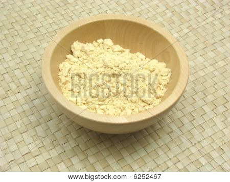 Wooden Bowl With Soy Meal On Rattan Underlay