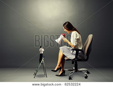 aggressive woman screaming at small man on the stepladder over dark background