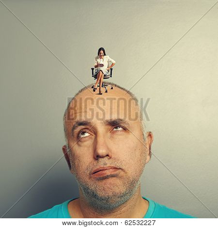 fatigued man and small angry woman on his head over grey background