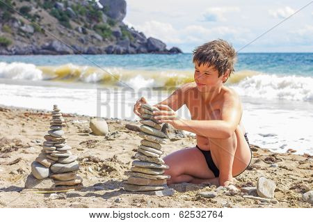 Sunburnt Boy Plays With Pebbles On The Beach