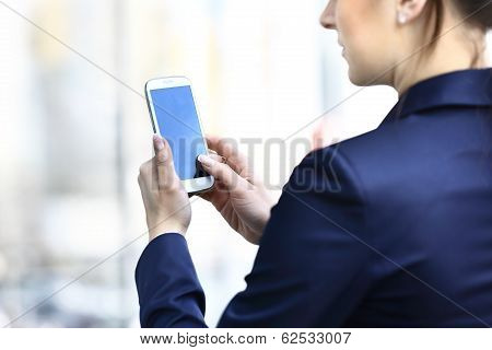 Businesswoman hands holding smartphone.