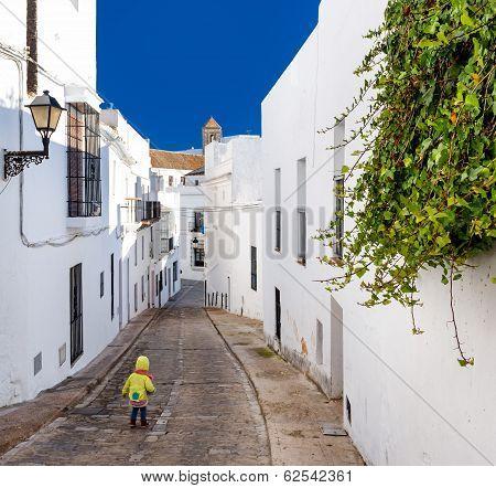 Baby Walking On Narrow Street Of Vejer De La Frontera. Costa De La Luz, Spain