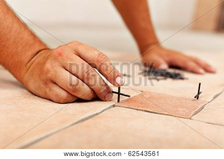 Worker Hands Placing Spacers Between Ceramic Floor Tiles